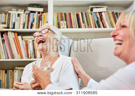 Nurse and happy senior woman laughing together in retirement home