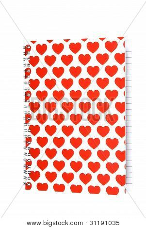 Notepad with hearts on cover on white background. Clipping path included.