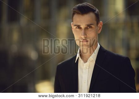 A portrait of a goodlooking young guy posing in the street. Men's beauty, fashion.