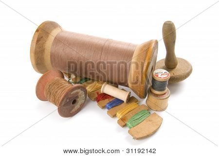 Antique bobbins with thread on a white background.