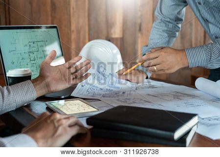 Confident Engineer Team Working With Blue Print With Architect Equipment Discussing And Planning Wor