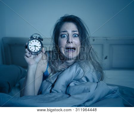 Attractive Woman In Bed Showing Alarm Clock To Camera Feeling Worried, Stressed And Sleepless