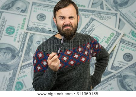 A Pensive Guy With A Beard And Glasses Against A Background With Dollars. Thinking About Question, P