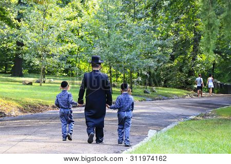 Religious Jew. A Family Of Hasidic Jews, A Man With Children, Walks Through The Autumn Park In Uman,