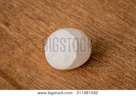 Round Small Gravel Of Sandstone Washed Round By The Waves Of The Sea On Wooden Underground