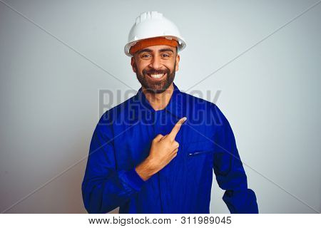 Handsome indian worker man wearing uniform and helmet over isolated white background cheerful with a smile of face pointing with hand and finger up to the side with happy and natural expression