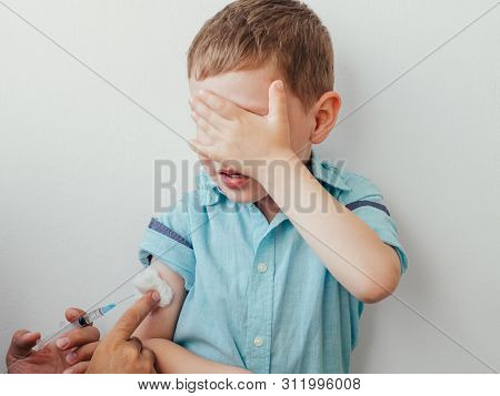 Little Boy Is Afraid To Vaccinate. Little Caucasian Baby Boy In Blue Shirt Covered His Eyes With Han