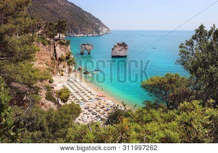 Summer Touristic Destination In Puglia, Italy: Faraglioni Di Puglia Baia Delle Zagare. Beach And Far