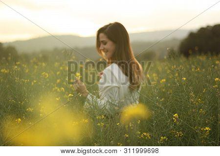 Beautiful Woman On Yellow Flowers Field With Dark Cloudy Sky