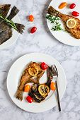 Grilled flounder fish served on white plate poster