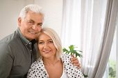 Affectionate senior couple with glasses of water in kitchen poster
