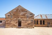 Sandstone brick convict built building with decorative stonework, corrugated iron roof, arched doorway, pebbled courtyard against clear blue sky poster