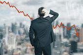 Back view of stressed young businessman looking at downward red arrow on blurry city background. Decrease, stats and economy concept. Multiexposure poster