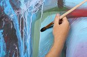 man hand painting beautiful bright artistic blue abstract picture poster
