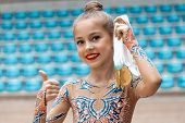 Winner of the rhythmic gymnastics competition, portrait of a pretty little girl holding in hand two gold medal and gesturing by thumbs up a good mood, happy sportive childhood poster