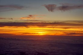 orange sky and clouds from an airplane window during an evening flight.