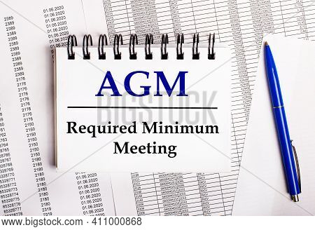 On The Table Are Charts And Reports, On Which Lie A Blue Pen And A Notebook With The Word Agm Annual