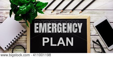 Emergency Plan Is Written In White On A Black Board Next To A Phone, Notepad, Glasses, Pencils And A