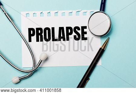 On A Light Blue Background, A Stethoscope, A Pen And A Sheet Of Paper With The Inscription Prolapse.