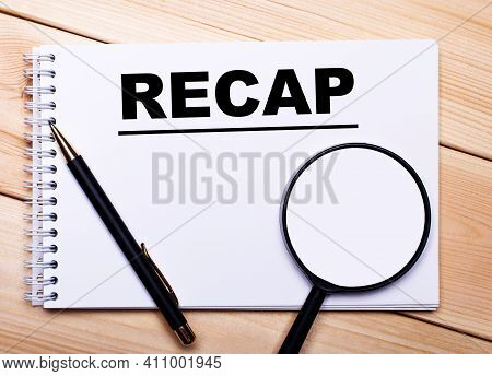 On A Light Wooden Background Lie A Pen, A Magnifying Glass And A Notebook With The Text Recap
