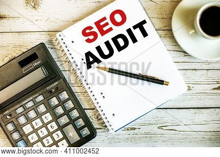 Seo Audit Written On White Paper Near Coffee And Calculator On A Light Wooden Table. Business Concep