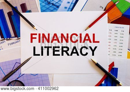 The Words Financial Literacy Is Written On A White Background Near Colored Graphs, Pens And Pencils.