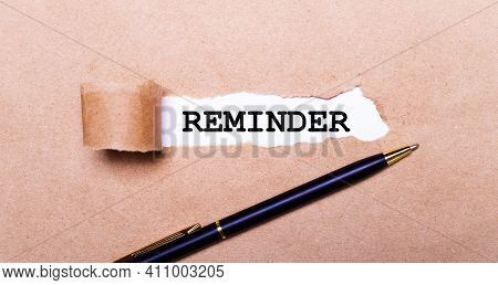 Torn Kraft Paper, White Background With The Text Reminder. Nearby Is A Black Handle. View From Above