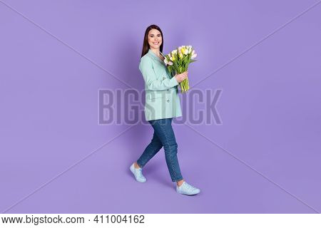 Full Size Profile Side Photo Of Brunette Woman Go Empty Space Hold Tulips Wear Jeans Isolated On Pur