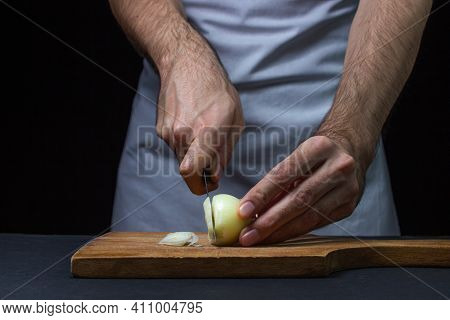 Onion On A Dark Background. The Cook Cuts The Onion On A Black Background. Slicing Onions