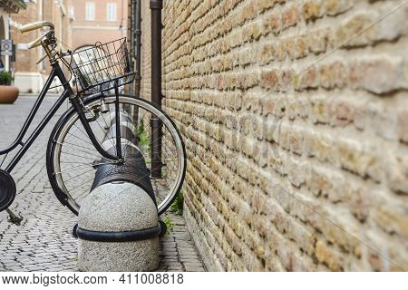 The front wheel of a retro bicycle stands near an old brick wall