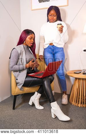 Young Businesswomen Of Black Ethnicity. Telecommuting And Having Fun With A Laptop From A Hotel Room