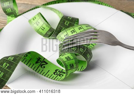 Close-up Of A Measuring Tape And A Fork On A Plate. Weight Loss Concept, Problem Of Excess Weight, O