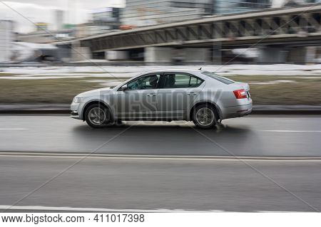 Moscow , Russia - March 3, 2021: Retired Elderly Man Driving Silver Skoda Rapid On City Street. Seni