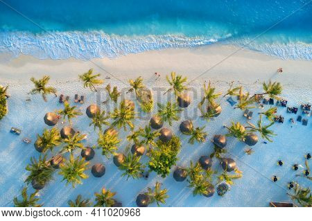Aerial View Of Umbrellas, Palms On The Sandy Beach Of Indian Ocean At Sunset. Summer In Zanzibar, Af