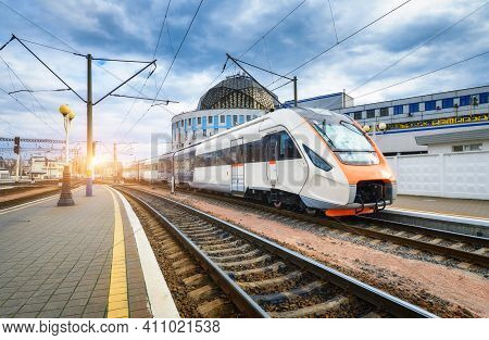 High Speed Train On The Railway Station At Sunset. Industrial Landscape With Moving Modern Intercity