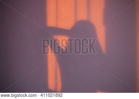 The Shadow Of A Woman Standing Near The Window With Her Hand Near The Head In The Morning At Dawn. T