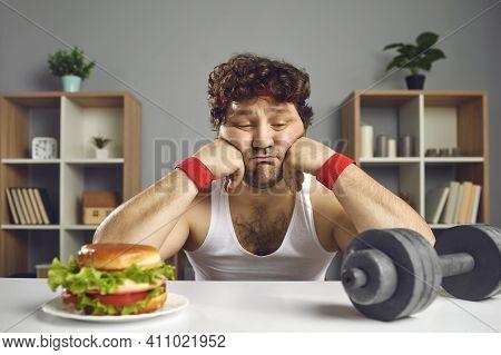 Sad Man Looking At Tempting Burger And Dumbbell Choosing Between Food And Training