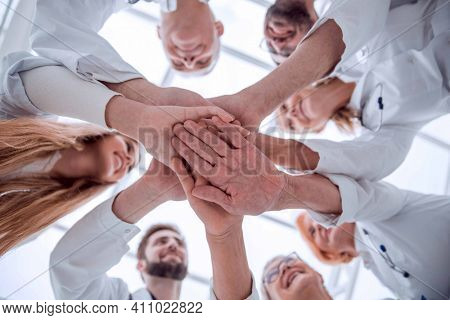 close up. group of different doctors putting their hands together