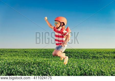 Happy Child Jumping Against Blue Sky. Kid Having Fun In Spring Green Field Outdoor. Portrait Of Boy