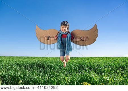 Happy Child Playing With Toy Wings Against Blue Sky Background. Kid Having Fun Outdoor In Spring Gre