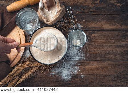 The Cooks Hand Stirs The Leaven. Flour, Sourdough, Water, Wheat On A Wooden Background.