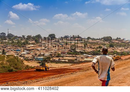 An African Man Runs For Exercise On A Dirt Road Next To Part Of The Kibera Slum In Nairobi, Kenya.