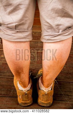 A Caucasian Girls Legs And Boots, As Seen From Behind, Covered In Red Dirt After A Long Dusty Hike.