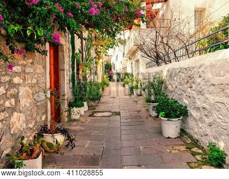 Cobbled Street With White And Stone Walls And Flowers