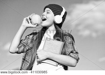 Taking Snack Break On Fresh Air. Small Kid Bite Apple On Blue Sky. Little Girl Enjoy Listening And R