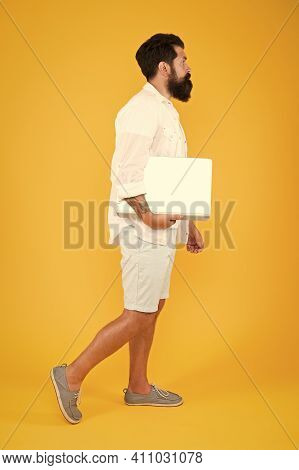 In Trendy Hipster Style. Hipster Hold Computer Yellow Backgrounf. Bearded Man With Hipster Beard In