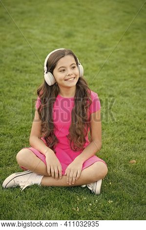 Look Cool And Sound Great. Cool Girl Listen To Music On Green Grass. Happy Child Use Headphones Outd