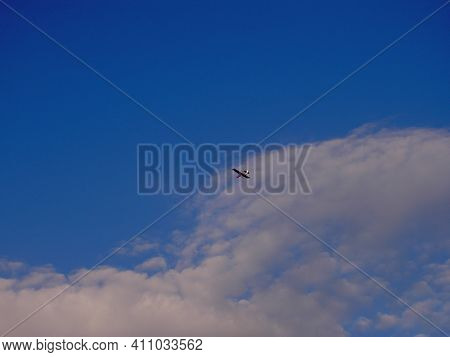 Very Small And Light Propeller Plane Flying At High Altitude, In The Background Of Blue Sky, View Fr