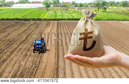 Hand With A Turkish Lira Money Bag On The Background Of A Farm Field With A Tractor. Subsidies Suppo