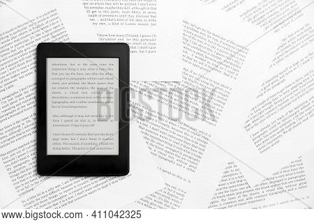Electronic Reader With The Screen On And A Text On It, On Sheets Of Paper With Text Printed On Them.